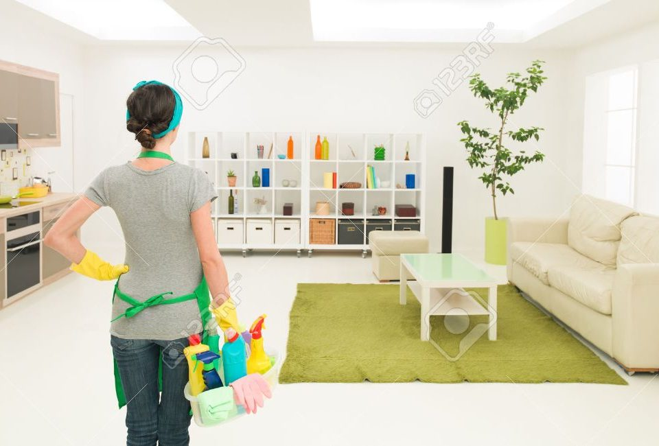 young-caucasian-woman-standing-in-clean-house-holding-cleaning-products